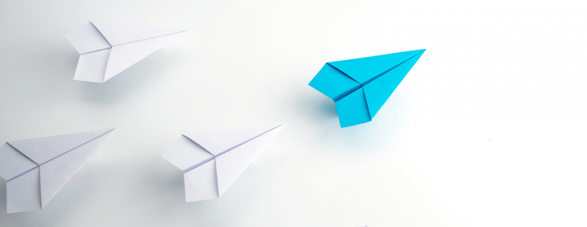 Blue paper plane in front of three other white paper airplanes, leader concept, white background.