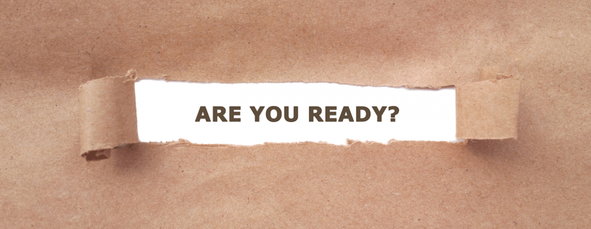 Brown paper that has been torn and pulled back revealing the words are you ready, on white paper that was underneath