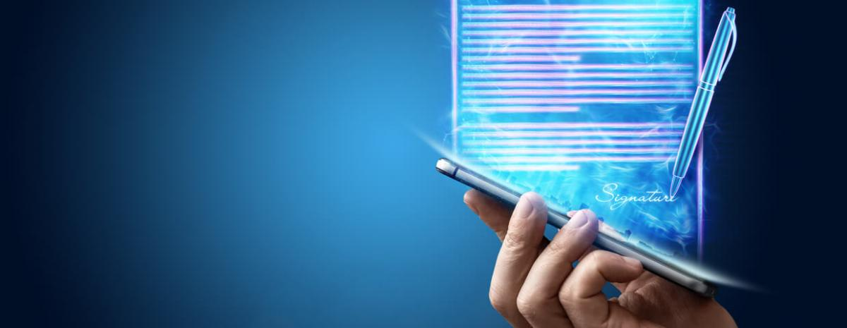 Hand holding smart phone with a holographic document and pen coming out of it.