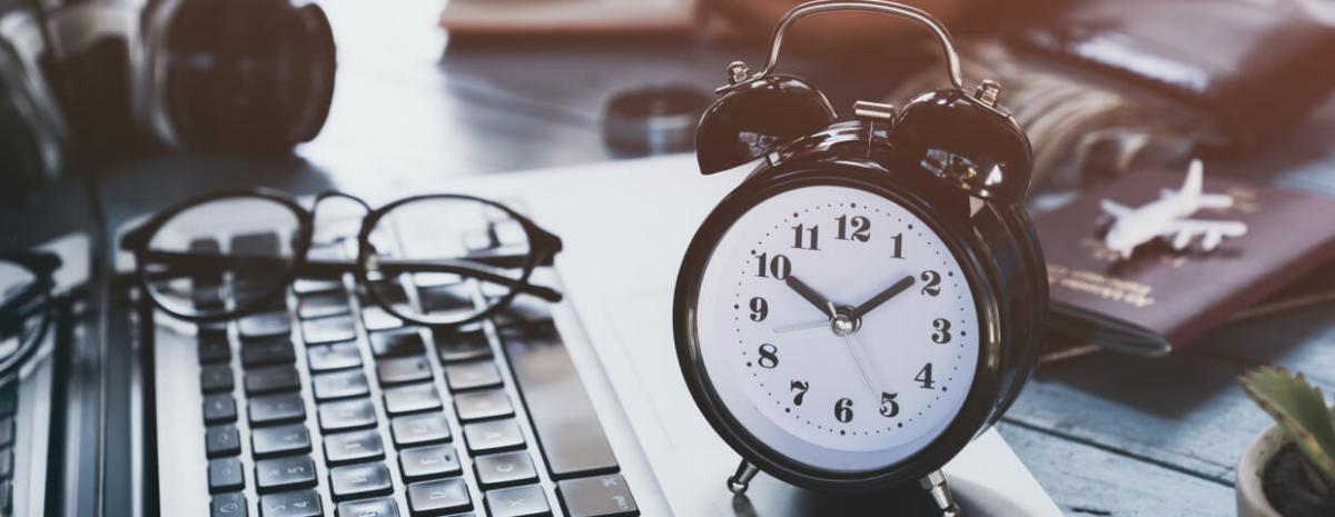 Clock next to laptop, glasses sitting on keyboard